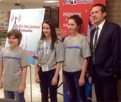 Le ministre de l'Éducation du Nouveau-Brunswick, M. Serge Rousselle, et les jeunes d'Acadiepédia. (photo : A. Miller)
